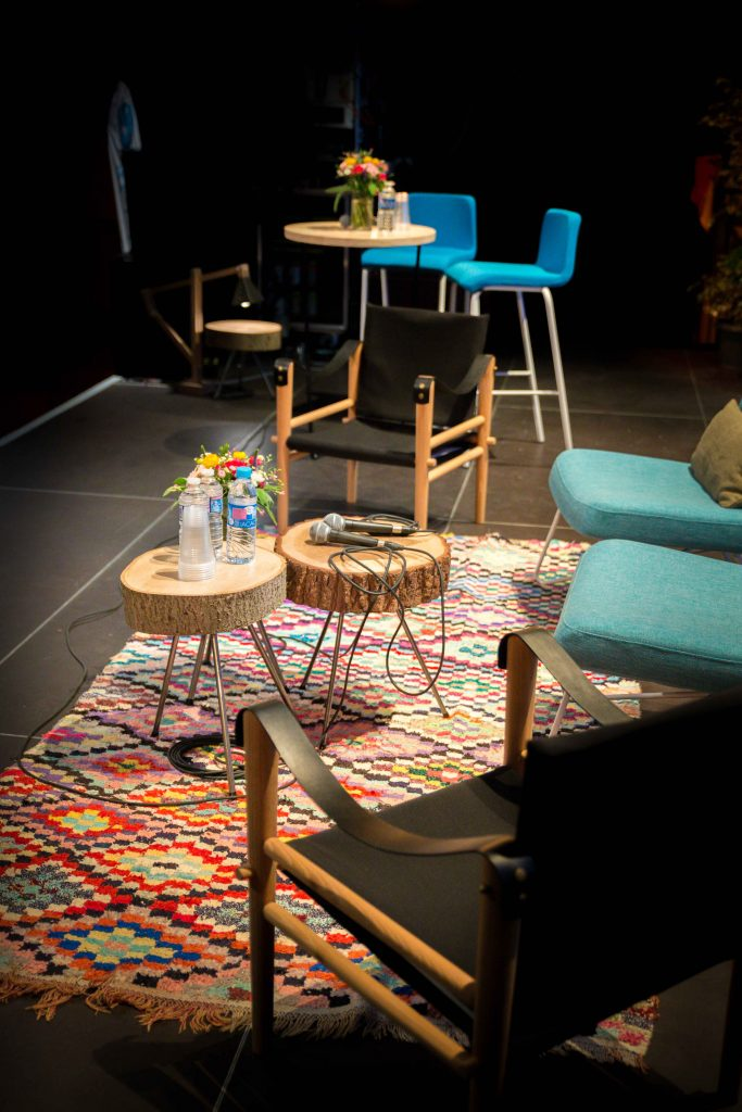 mobilier sur scène : tapis boucherouite, tables en rondins de bois, fauteuils et mange-debout, agence Parade