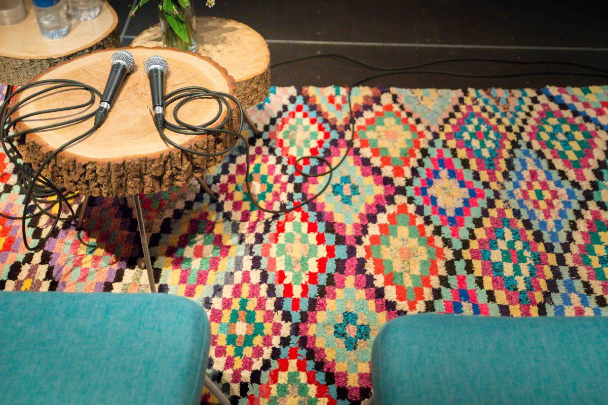 tapis boucherouite motifs roses, fauteuils en tissu bleu tables en rodin de bois et micros, agence Parade