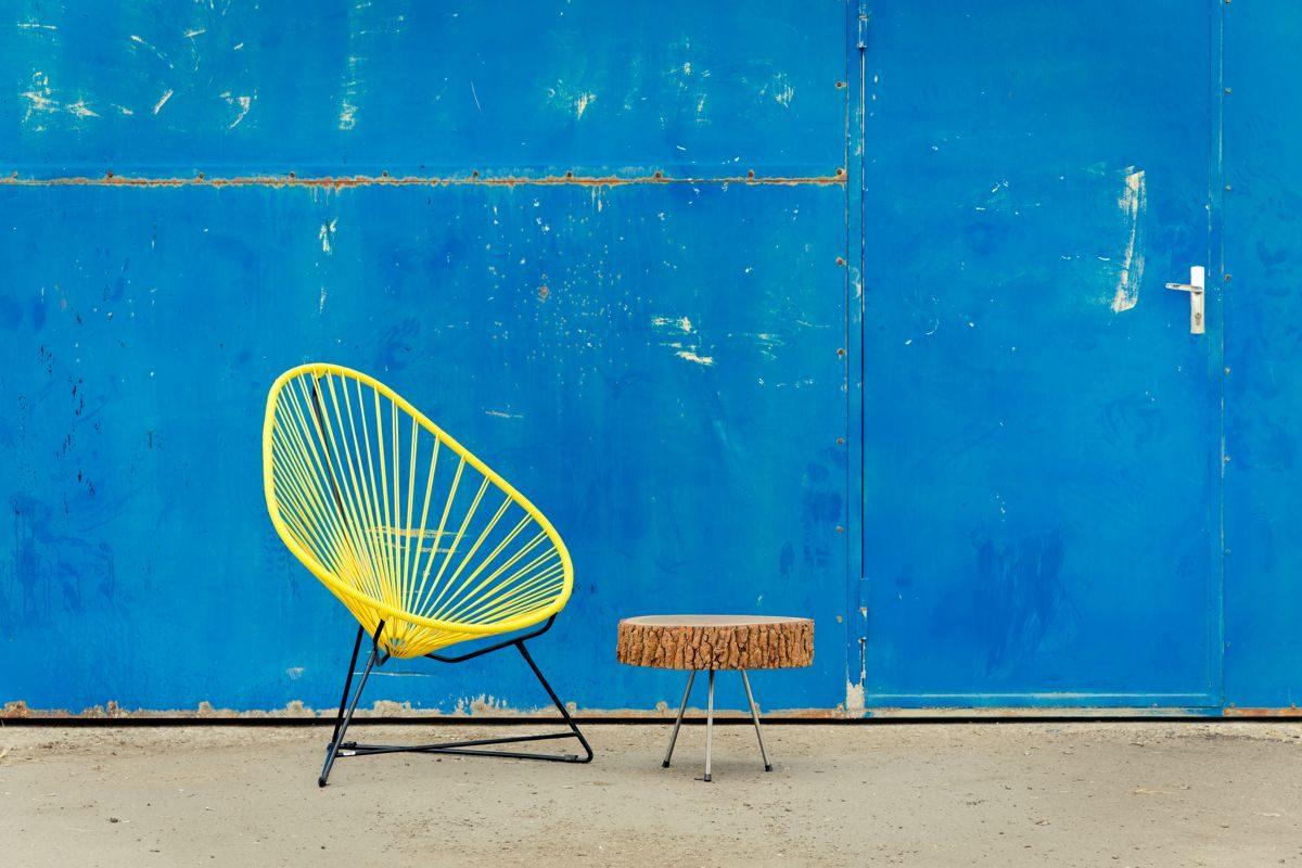 fauteuil Acapulco jaune, de la marque Boqa, table basse en rodin de bois, portail bleu industriel, agence Parade