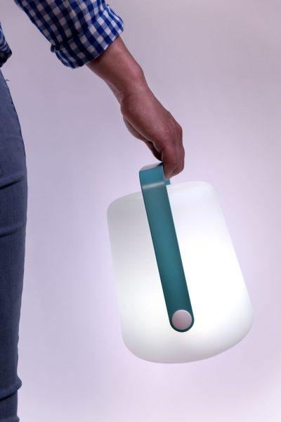 lampe nomade blanc et poignée turquoise de la marque Fermob, agence Parade