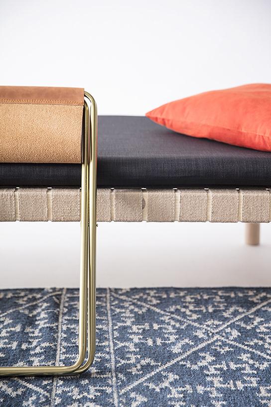 tapis kilim bleu, banquette en bois et sangles jute, matelas en tissu gris, oreiller orange, tabouret en métal doré et assise cuir, agence Parade