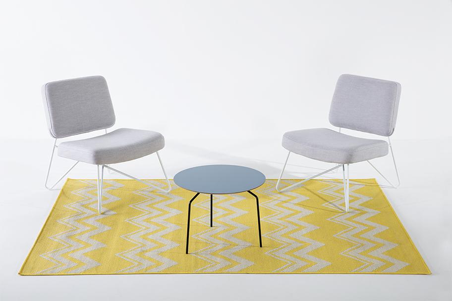 tapis jaune et blanc, fauteuils en tissu gris et pieds métal blanc, table basse bleue et pieds métal noir Bo Concept, agence Parade