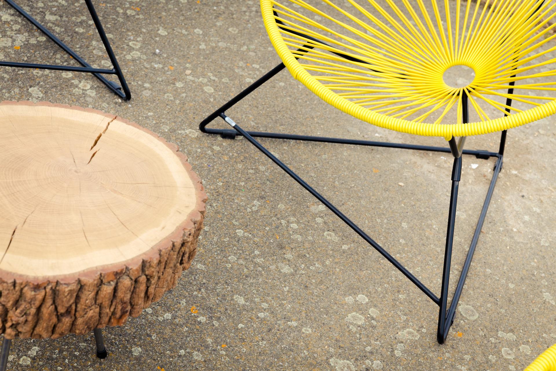 fauteuil acapulco jaune et table basse en rondin de bois agence Parade