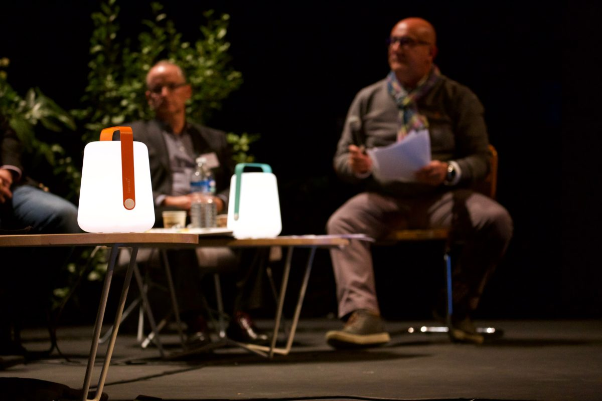 tables basses, lampes Fermob et personnes assises, conférence, agence Parade