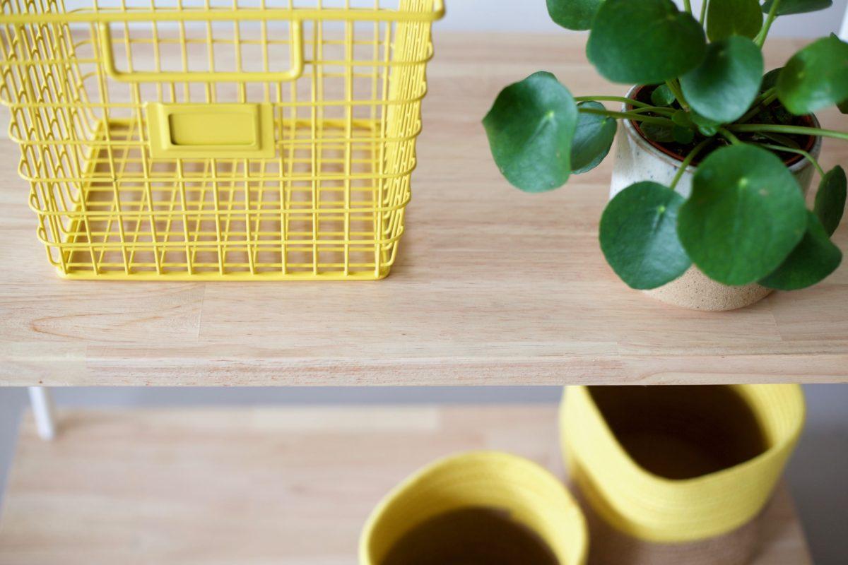 corbeille en métal jaune, plante verte et étagère en bois agence parade